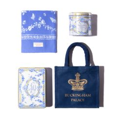 A blue bag with a gold crown and 'Buckingham Palace' is stood on a gold cake stand. Next to this is the Royal Birdsong tea caddy and biscuit tin. There is also a white vase with eucalyptus in the middle and a cup of tea on a blue tea towel