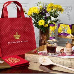Red bag featuring a gold crown and the words 'Buckingham Palace'. It is next to a gold tray containing a cup of tea, egg in an egg cup, purple and yellow tea box and purple and yellow biscuit tube. There is also a red apron on the left and a wooden spoon.