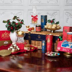 Against a white background is a wicker hamper with leather buckles and a navy blue lining printed with a gold crown and the words 'Buckingham Palace.' To the left is a folded red apron embroidered with a gold lion and unicorn and the words 'Buckingham Pal
