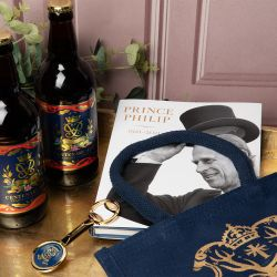 a creative set up of a navy juco bag, two bottles of centenary ale, the Prince Philip: A Celebration publication and a gold bottle opener with a blue circle with Prince Philip's cipher. Eucalyptus is placed behind the ales. The whole set is on a gold tray