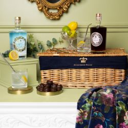Brown wicker hamper surrounded by a bottle of sloe gin and dry gin. There is a jar of lemons and limes on top of the hamper, next to a glass of gin and tonic with a metal straw. At the front of the hamper is a tray of rose and violet creams, next to a sec