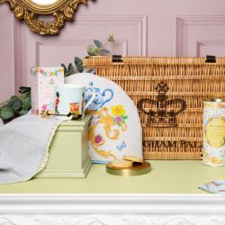 Wicker hamper on a pink panel background surrounded by eucalyptus, printed mug, gold spoon, floral box of tea and floral tube of biscuits and some biscuits scattered in front of the hamper